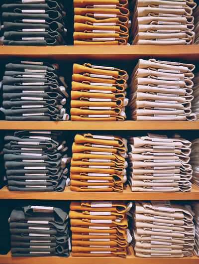 Full frame shot of folded clothes in shelf at store for sale
