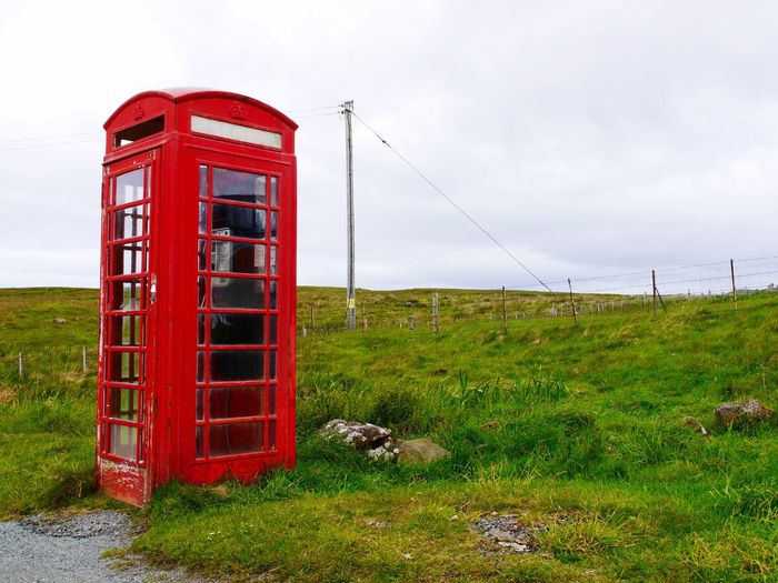 Red Telephone Booth On Grassy Field Against Sky