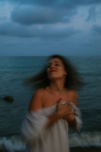 Beautiful young woman standing at sea against sky