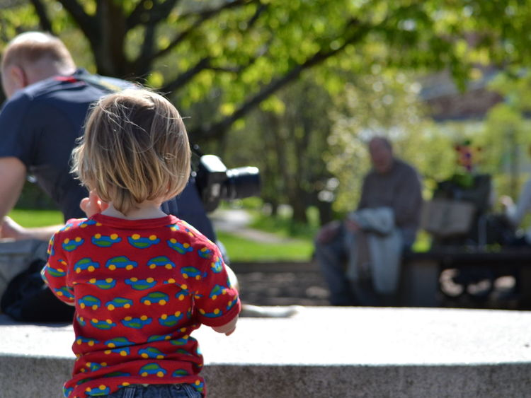 What's the plan? A Child's Perspective A Day In The Park Child Focus On Foreground Leisure Activity Lifestyles No Identifiable People Park Park Life People In The Background People Watching Rear View Selective Focus