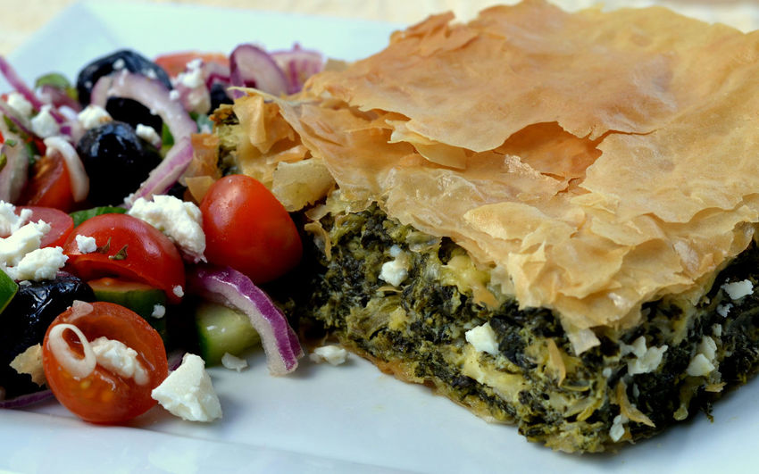 Closeup of Spinach and Feta Cheese Pie (Spanakopita) made with Filo Pastry and served with Traditional Greek Salad: High Angle Profile Appetiser Dinner Filó Greek Greek Salad Mediterranean Food Appetizer Close-up Feta Fetacheese Filo Pastry Flaky Pastry Food Food And Drink Greek Food Meal Ready-to-eat Serving Size Snack Spanakopita Spinach Spinach Pie Traditional Traditional Greek Food Wellbeing