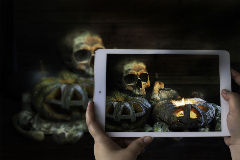 Photographing with smartphone in hand Skull bones concept with lighting candle and pumpkins in the dark night on old wooden plate and wooden background / Still life style Wooden Background Evil Ghost Pumpkins Body Part Bone  Close-up Dark Night Dead Finger Graveyard Hand Holding Human Body Part Human Finger Human Hand Indoors  Lifestyles Lighting Candle One Animal One Person Pet Owner Photography Themes Scary Smartphone