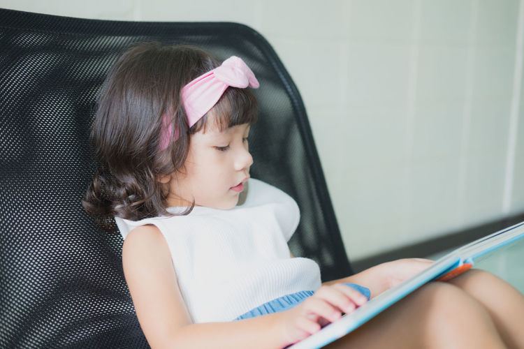 Girl looking away while sitting on book at home