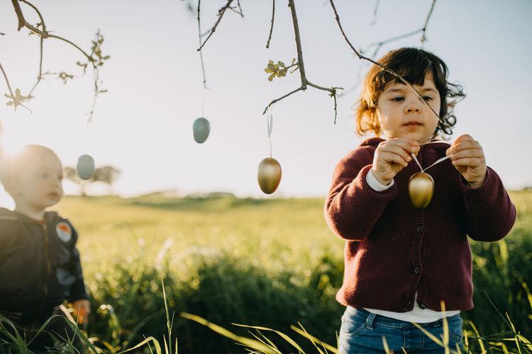 Full length of girl hanging easter eggs on tree