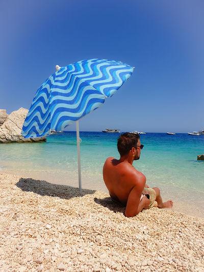 Shirtless man looking away while relaxing at beach