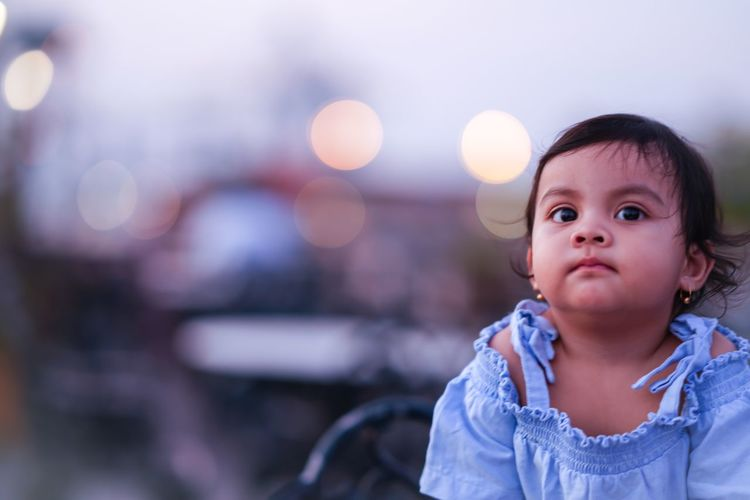 Cute baby girl looking away in city at sunset