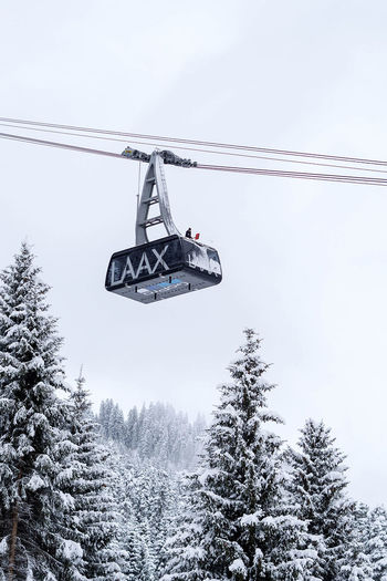 Man cleaning the cable car Cold Temperature Day Laax Nature Outdoors Overhead Cable Car Ski Ski Lift Snow Snowboarding Space For Text Sport Switzerland Tree Winter