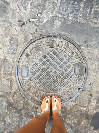 Low section of woman standing on manhole