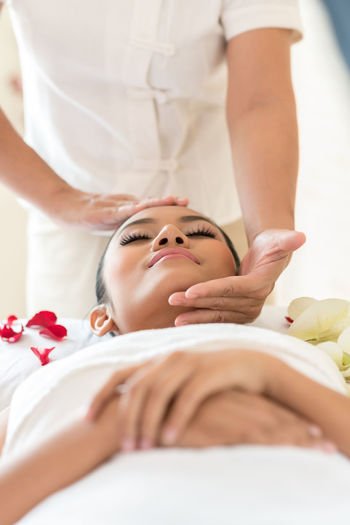 Therapist Massaging While Woman Sleeping On Bed At Spa