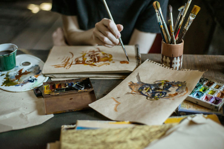 Creativity Art And Craft Brush Paintbrush Craft Human Hand Artist Table Indoors  Occupation Selective Focus One Person Paint Human Body Part Skill  Palette Hand Studio Drawing - Activity Workshop Art And Craft Equipment Design Professional Watercolor Paints