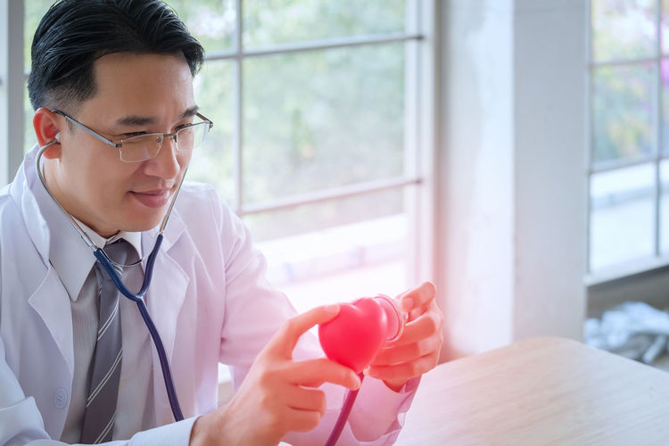 Doctor listening heart through stethoscope at hospital