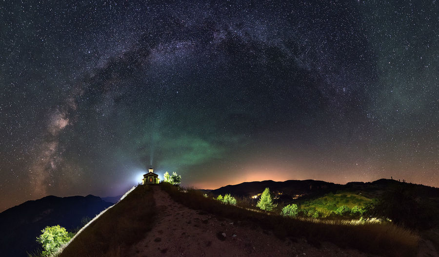 Distant view of illuminated chapel on mountain against star field