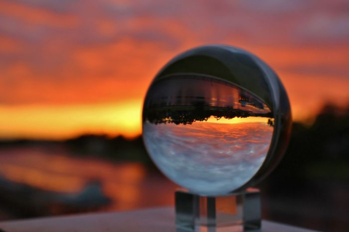 Vibrant orange and yellow sunset skies captured in a crystal ball with refracted light. Sunset On The Water Sunset_collection Close-up Colorful Clouds Colorful Sky Crystal Ball Photography Day Nature No People Orange Color Orange Sky Sunset Outdoors Puffy Colorful Clouds Reflection Refraction Sky Sunset Vibrant Colors Water Yellow Sky