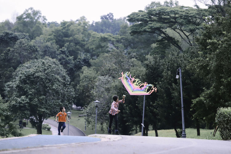 Boys flying kite while running on road by trees