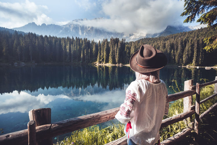Rear view of woman looking at trees by lake against mountains