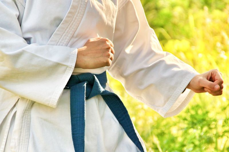 Midsection of woman doing karate practice outdoors