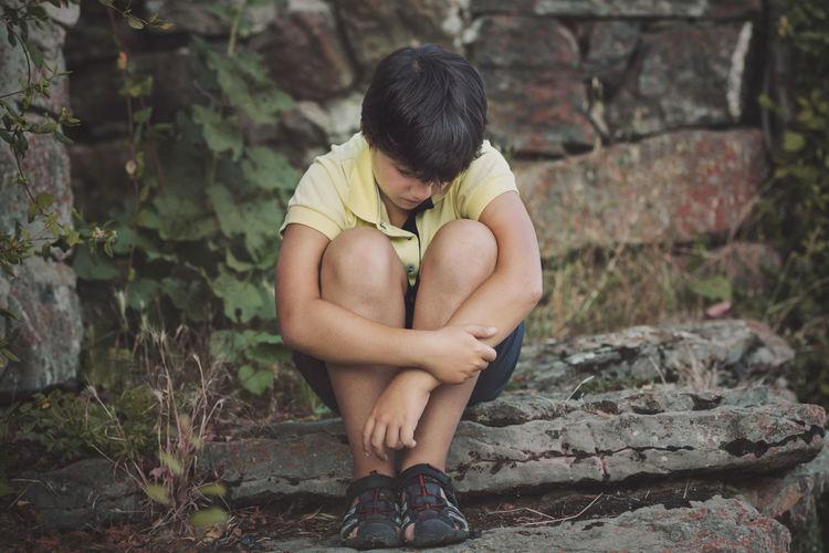 Sad boy sitting against stone wall