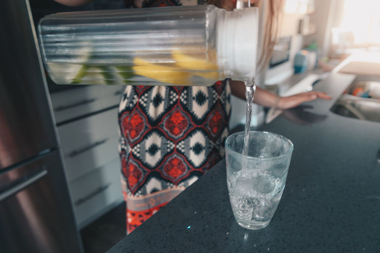 Cropped image of woman pouring lemonade in glass at table
