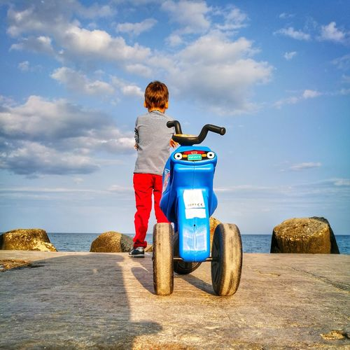 Rear View Of Boy Standing With Tricycle On Promenade Against Sky