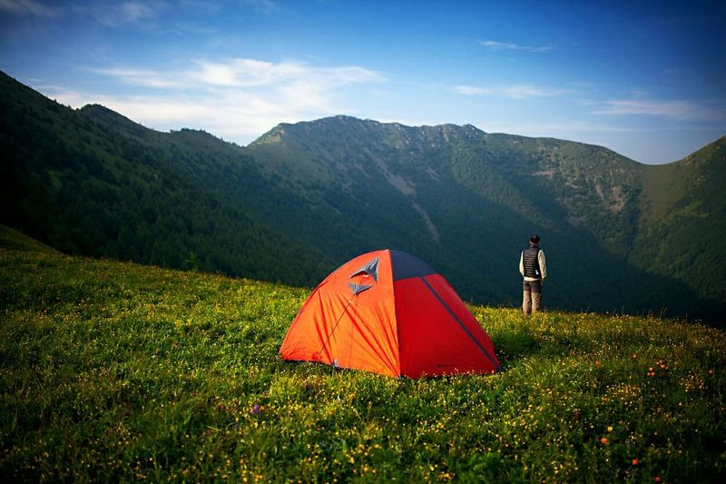 Tent on grassy field against mountains