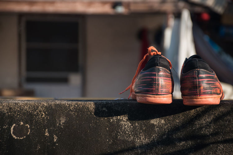 Close-up of shoes on retaining wall against building