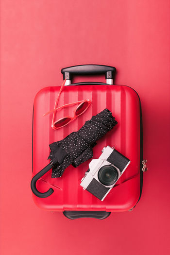 Red travel suitcase with red sunglasses, old camera, black umbrella on red background. Minimal style Red Indoors  Still Life Bag Case Travel Umbrella Camera Sunglasses Departure Holiday Traveling Journey Luggage Trip Vacations Voyage Transport Red Suitcase Recreation  Flat Lay Overhead View