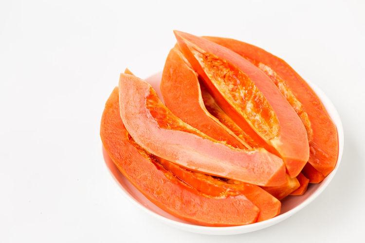 Close-up of orange slice over white background
