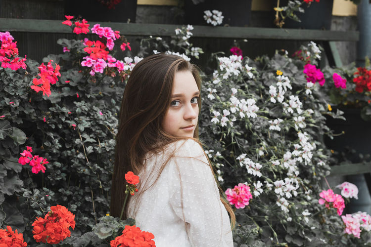 Portrait of young woman standing by flowering plants