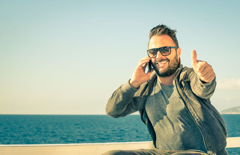 Man showing thumbs up while talking on smart phone against sky