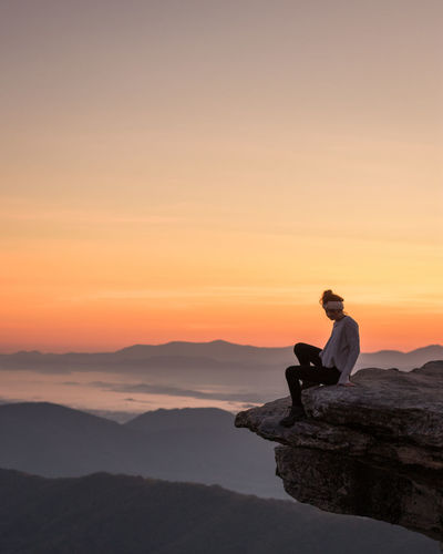 McAfee Knob Beauty In Nature Leisure Activity Lifestyles Nature One Person Outdoors People Real People Relaxation Rock - Object Scenics Silhouette Sitting Sky Sunrise Sunset Tranquil Scene Tranquility Young Adult