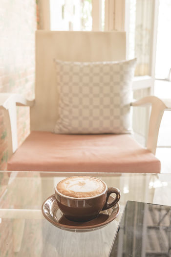 Coffee cup on table by chair in cafe