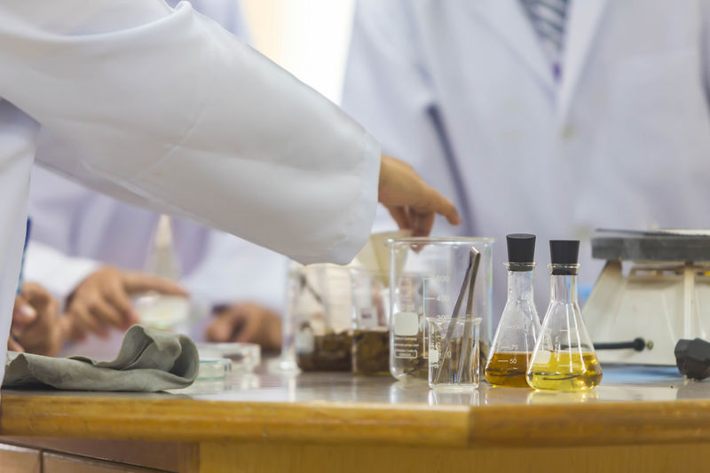 Young scientists are doing experiments in science labs. Analyzing Clothing Coworker Education Hand Healthcare And Medicine Human Body Part Human Hand Indoors  Lab Coat Laboratory Medical Research Men Midsection Occupation Real People Research Science Scientific Experiment Scientist Uniform Working