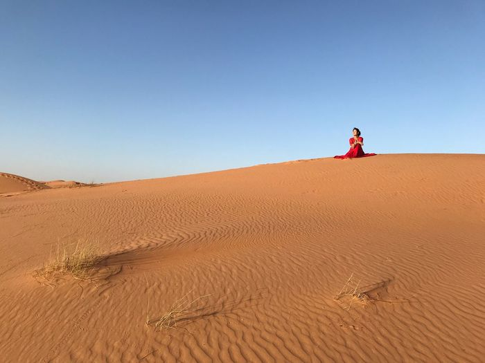 Woman Sitting On Sand Against Sky