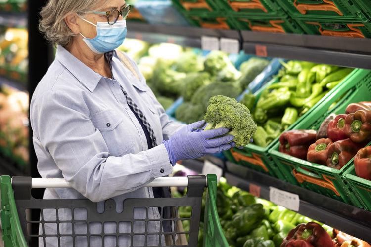 Woman wearing mask buying vegetables at supermarket