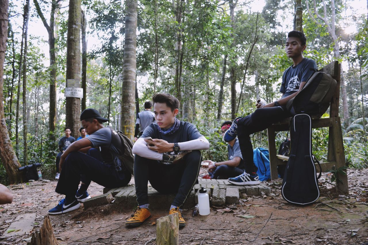sitting, young men, real people, young adult, tree, mid adult men, full length, forest, leisure activity, casual clothing, lifestyles, togetherness, day, men, relaxation, nature, young women, two people, outdoors, growth, technology, friendship, people