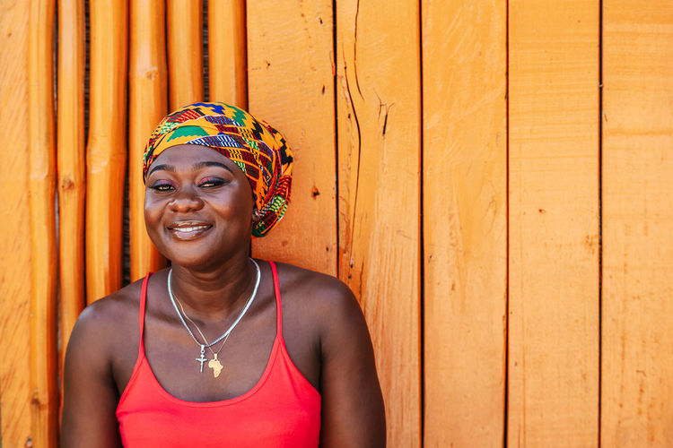 African woman with a hopeful happy smile standing against a painted wooden wall