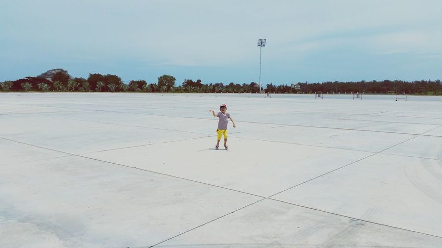 Man skateboarding on beach against sky
