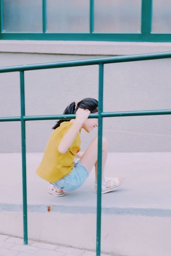 Side view of woman against yellow railing