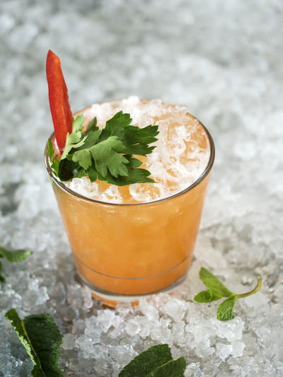 Close-Up Of Drink Garnish With Bell Pepper And Herb In Glass On Crushed Ice