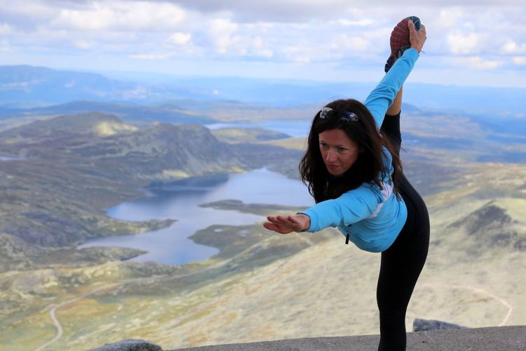 Woman doing standing bow pulling yoga pose and meditation on top of Gaustatoppen, Telemark, Norway. Standing Bow Stehender Bogen Yoga Outdoor Yoga Pose Yogagirl Young Adult Travel Destinations Yoga Hatha Yoga Individuality Yoga Post Beautiful People Yoga Practice Peace Of Mind Mountain Range Looking At Camera Human Body Part Beautiful Woman Water Adult Beauty Adults Only Photography Themes