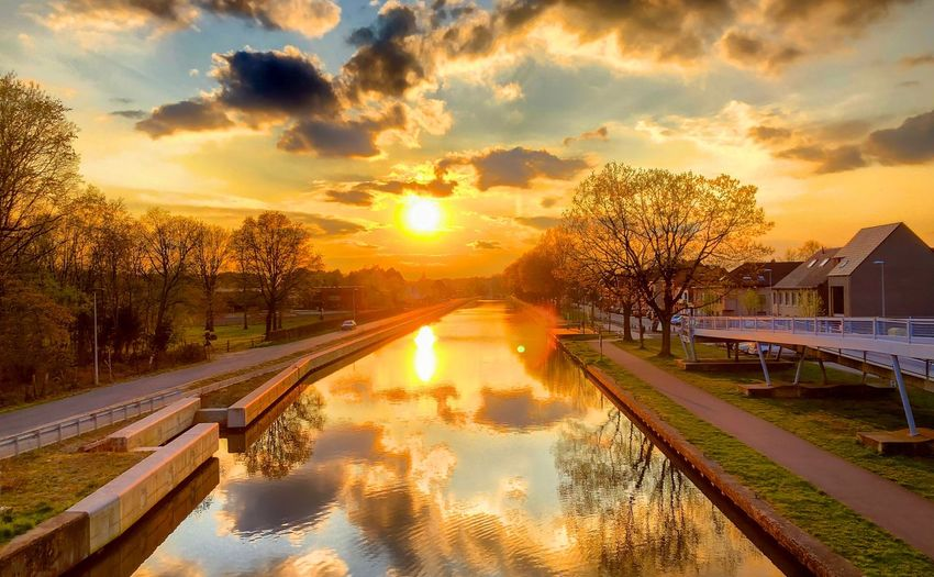 Golden sunrise or sunset with Fluffy white and dark clouds over a Countryside landscape reflected in the water of the river or canal Sunset Sky Water Cloud - Sky Reflection Nature Orange Color Architecture Transportation Beauty In Nature Sun Tree Plant Scenics - Nature Sunlight Built Structure Outdoors No People