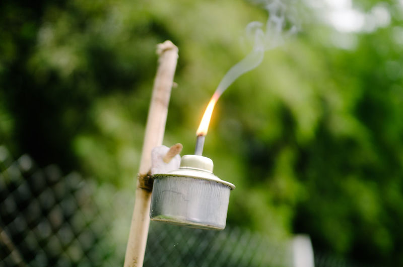 Close-up of burning candle against blurred background