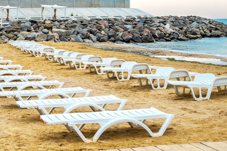 Empty chairs on sand at beach