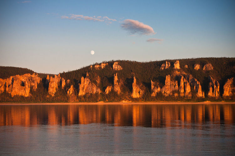 Scenic View Of Full Moon And Rock Formations Relfected In Calm Lake