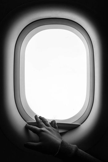 Cropped Image Of Person Hand On Airplane Window