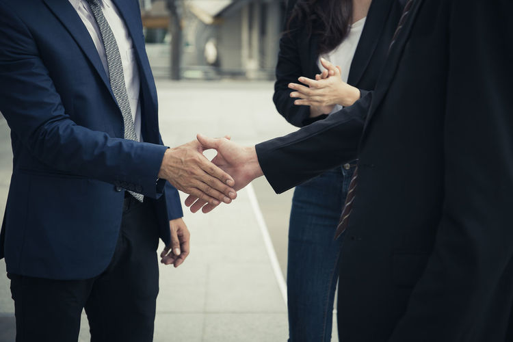 Businessmen shaking hands while standing by colleague in city