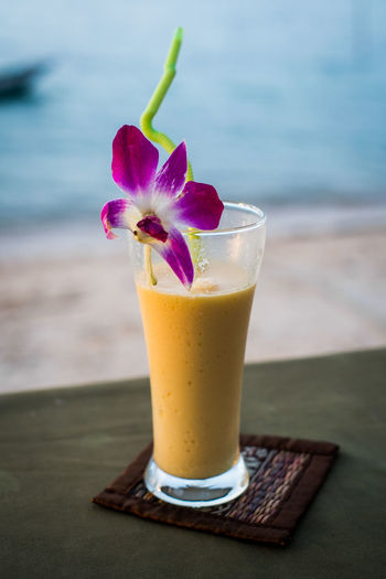 Close-up of mango smoothie with flower served on table at beach