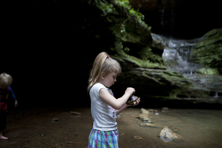 A five-year-old girl plays with a rock near the waterfall at Ferne Clyff State Park near Golconda, Illinois. Blond Hair Casual Clothing Childhood Ferne Clyffe State Park Girls Illinois Illinoisphotographer Leisure Activity Lifestyles Nature Nature One Person Outdoors Outdoors Photograpghy  Real People Rocks Southern Illinois  Standing Stream Vacation Water Waterfall