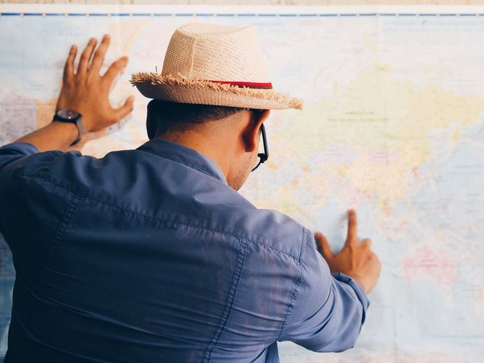 Rear view of man pointing on world map