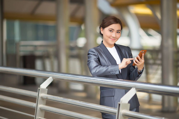 Businesswoman use smartphone Business Person One Person Standing Woman Suit Business Portrait Happy Smile Attractive Cheerful Manager Confident  Businesswoman Smiling Work Elégance Thinking About Life Positive Emotion Thoughtful Gorgeous Thinking Happiness Outdoor Smart Phone